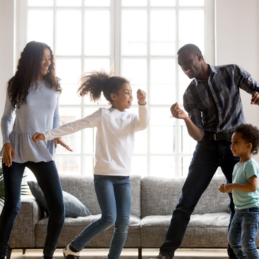 picture of family dancing in living room for self-care activities