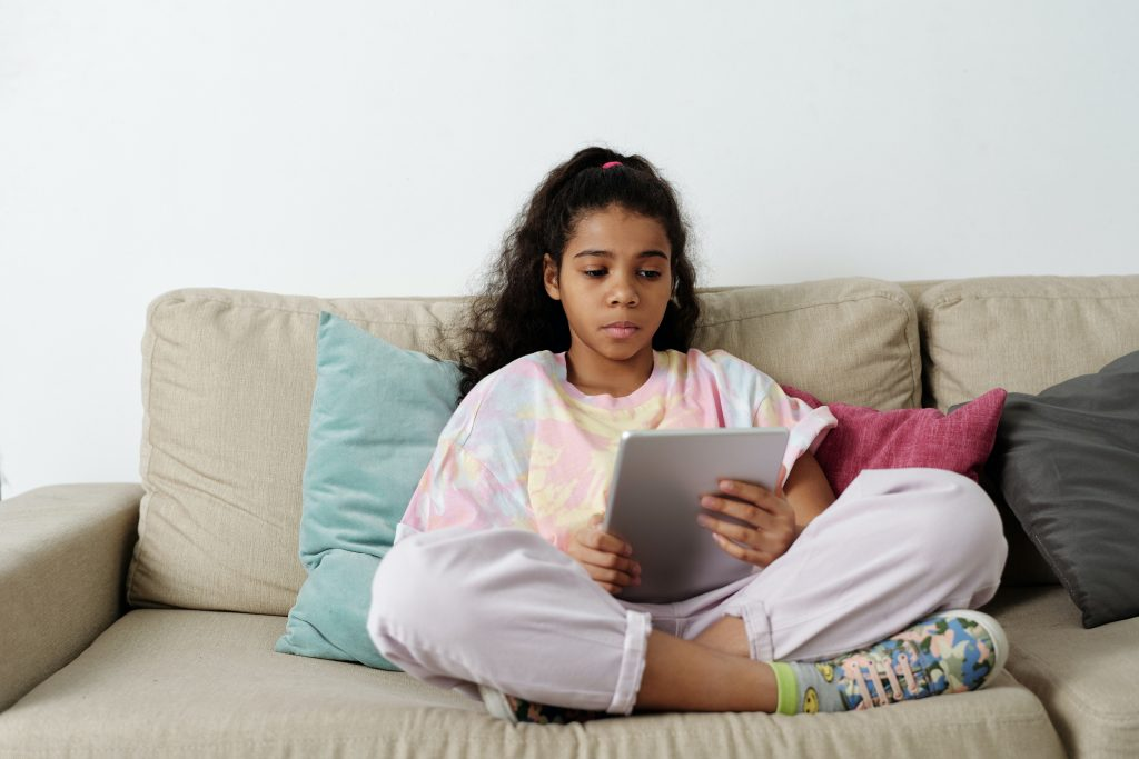 picture of a girl on her tablet sitting on the couch 7 self-care/activities for kids during lockdown